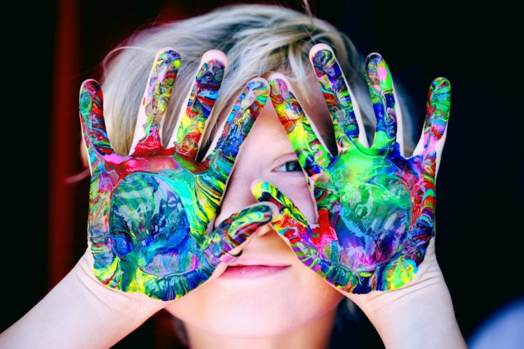 fille heureuse jouant avec de la peinture